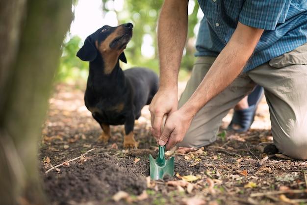 森の中でトリュフのキノコを探しているトリュフハンターと彼の訓練された犬