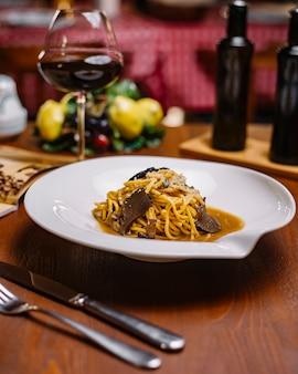 Spaghetti al tartufo con salsa di funghi e parmigiano grattugiato servito con vino rosso