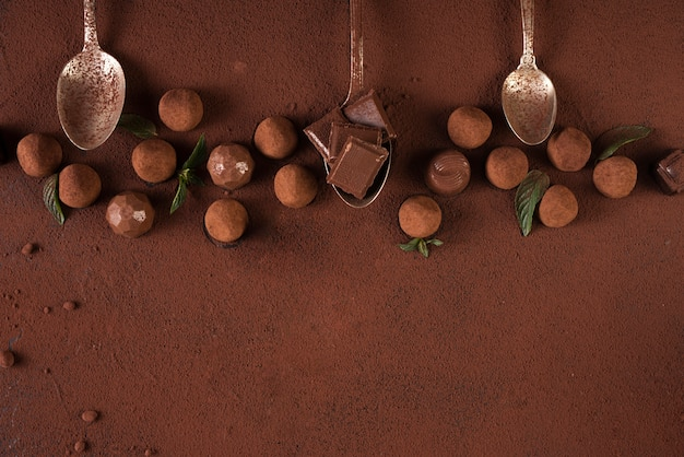 Truffles with chocolate bar squares and spoons anc copy space