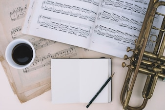 Trumpet and sheet music near drink and notepad