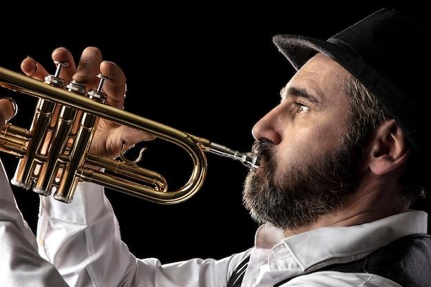 Trumpet man with beard portrait on black