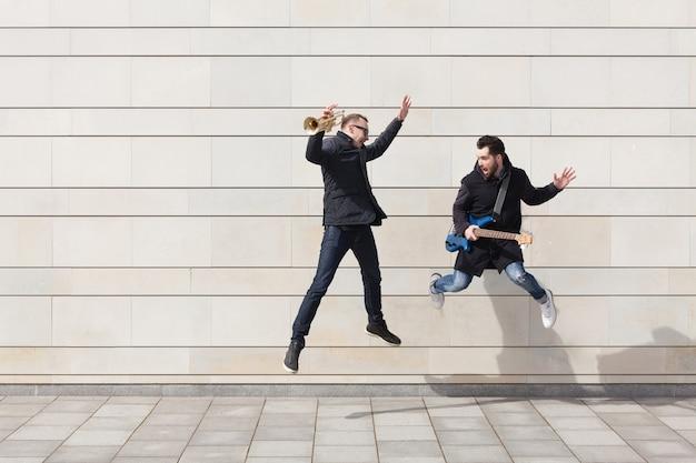 都市環境で飛ぶトランペットの演奏者とギタリスト
