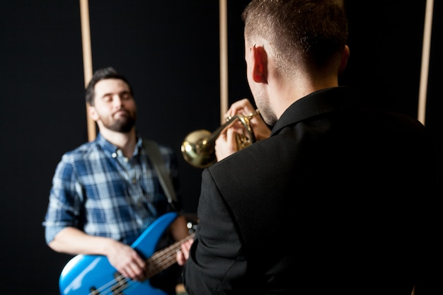 Trumpet player and guitarist on chair