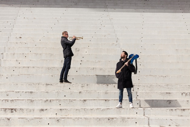 Trumpet player and guitarist on concrete stairs
