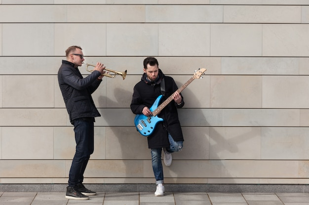 Trumpet player and guitarist playing in front of wall