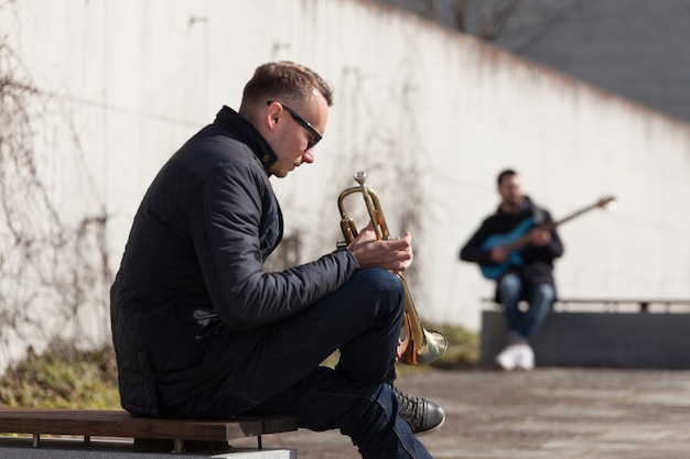 Trumpet player and guitarist sitting in urban environment