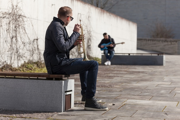 Trumpet player and guitarist sitting