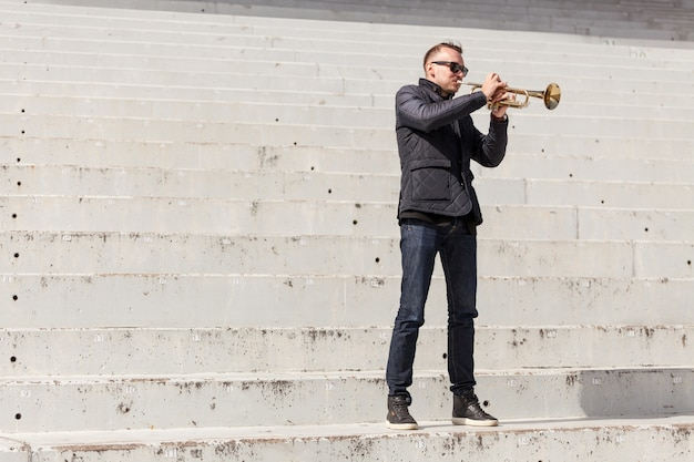 Trumpet player standing on stairs