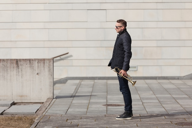 Trumpet player in urban environment side view