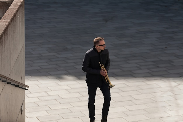 Trumpet player walking upstairs and looking to his left