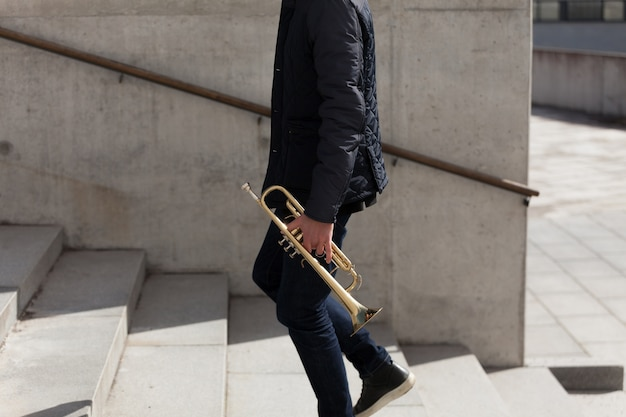 Trumpet player walking upstairs side view