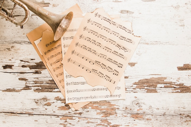 Trumpet and sheet music on old table