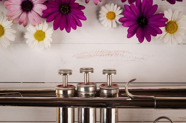 Труба с цветами в деревянном фоне