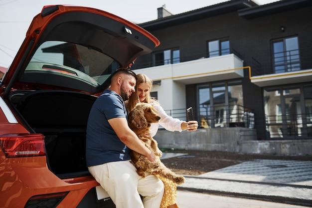 トランクが開いています。素敵なカップルが車の近くで犬と一緒に屋外で散歩をしています。