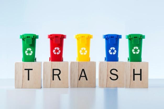 灰色の背景の上の木のブロックとゴミ箱に書かれたゴミ箱の単語。リサイクル、エココンセプト。