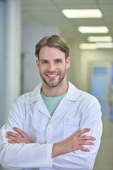 Trust, medicine. smiling young adult attractive man in white coat standing with arms crossed in illuminated corridor of clinic