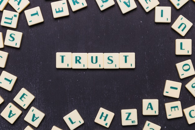 Trust word arranged on black background surrounded by scrabble letters