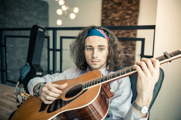 Надежная акустическая гитара. бесстрастный темноволосый артист с голубыми глазами и черной щетиной проводит время со своей гитарой
