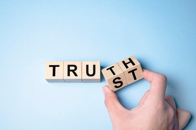 Truth instead of trust. hand turns dice and changes the word trust to truth.