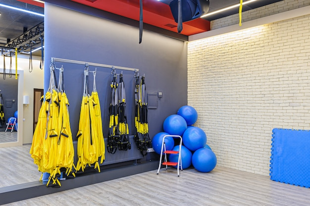 Trx straps and fitness balls in modern gym
