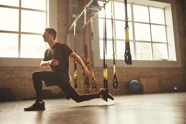 Trxトレーニング。ジムでtrxフィットネスストラップとスポーツウェアトレーニング脚の若い運動選手