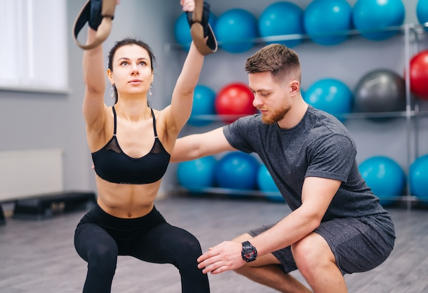 魅力的な女性がフィットネスセンターでtrxを使用して練習するのを支援する筋肉弱気トレーナー。