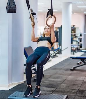 ジムでtrxストラップでトレーニングの女性。エクササイズを行う完璧なボディを持つ少女。健康的な生活のコンセプトです。閉じる。