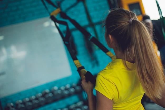 Trxによるトレーニング。フィットネストレーニングを作るジムで若い女性
