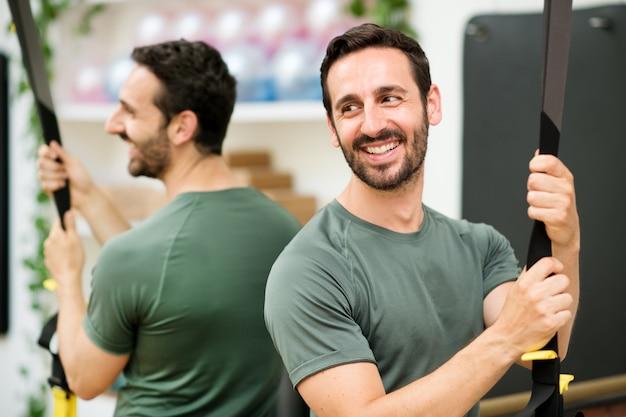 Жизнерадостный человек пригонки держа ленту trx на спортзале