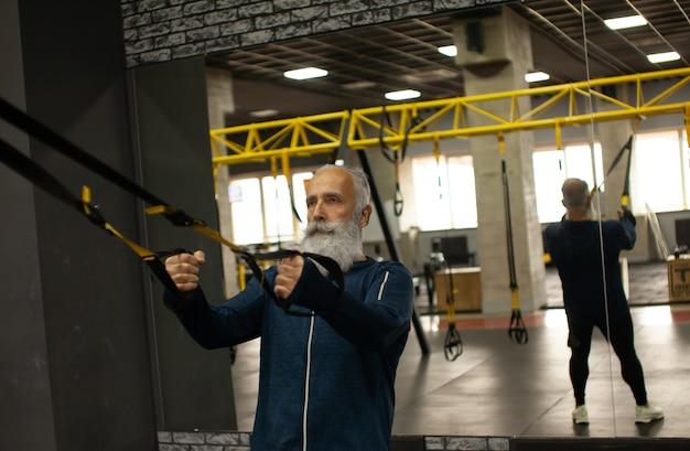 Тренировка бородатого старшего спортсмена с диапазонами сопротивления trx в спортзале.