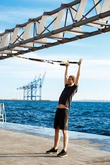 朝の海の近くのtrxでトレーニング陽気な若者