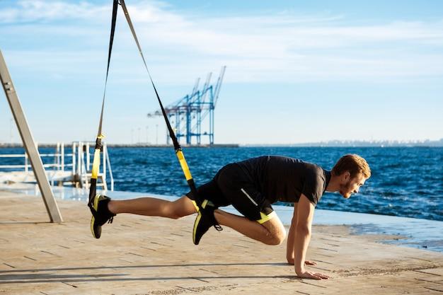 陽気な若者が午前中に海の近くのtrxでトレーニングします。