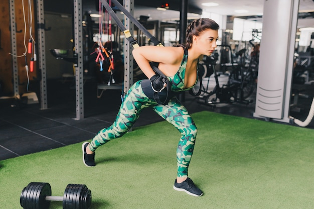 Концепция trx. красивая дама тренирует свои мышцы с помощью подвесного стропа или подвесных ремней в тренажерном зале