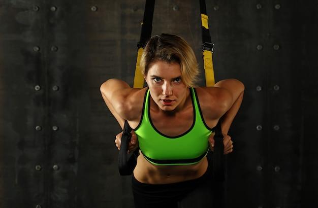 Молодая женщина с фитнес-ремнями trx