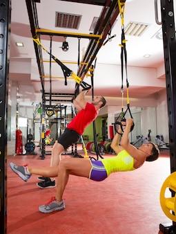 ジム女と男でフィットネスtrxトレーニング演習