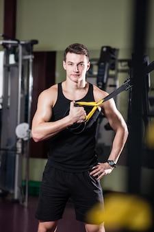 若い男はtrxのスポーツホールに従事しています。