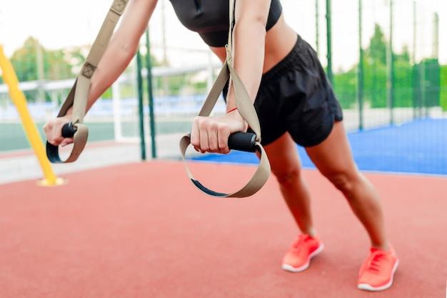 屋外のスタジアムでtrxトレーニングを行うスポーティなフィットネス女性