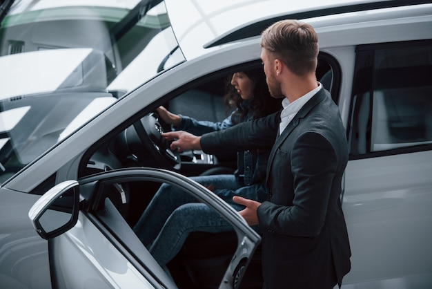 Try how it feels. female customer and modern stylish bearded businessman in the automobile saloon