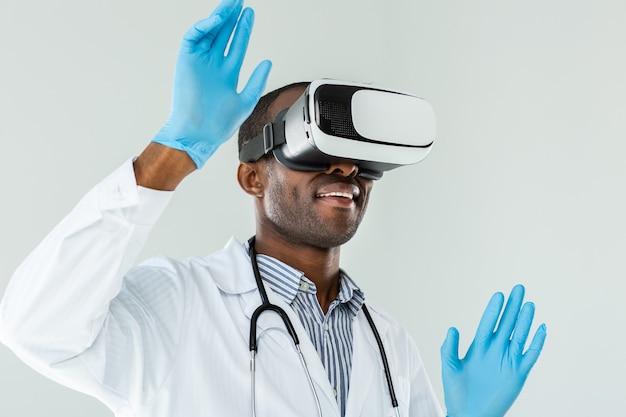 Попробуйте в действии. веселый улыбающийся врач, тестирующий очки vr, стоя на белом фоне Premium Фотографии