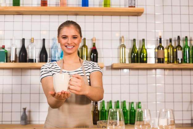 それを試してみてください。カウンターに立って、コーヒーを提供しながらあなたを見ている幸せな素敵な喜んでいる女性