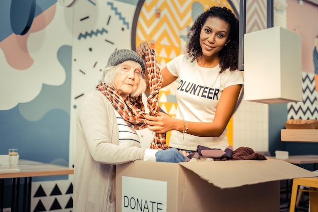 試着する。ホームレスの女性がスカーフを着用するのを手伝いながら笑っている楽しいアフロアメリカ人女性
