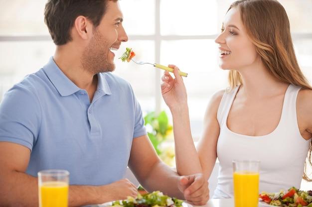 내 식사를보십시오! 여자가 그녀의 남자 친구에게 샐러드를 먹이는 동안 테이블에 함께 앉아 있는 아름다운 젊은 부부