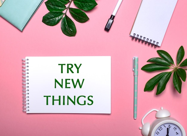 Try new things is written in green on a white notepad on a pink surface surrounded by notepads, pens, white alarm clock and green leaves