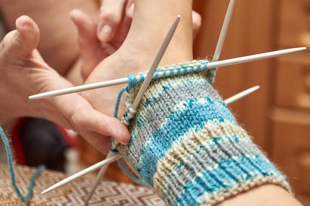 編みながら赤ちゃんの足に靴下を試してみてください。年配の女性の趣味は編み物です。セレクティブフォーカス
