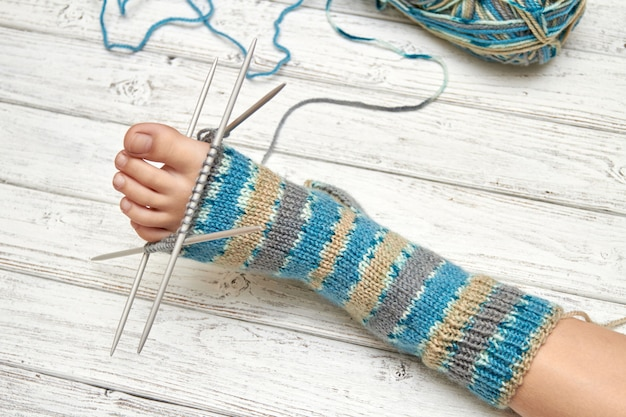 編みながら赤ちゃんの足に靴下を試してみてください。軽い木製の背景、セレクティブフォーカス