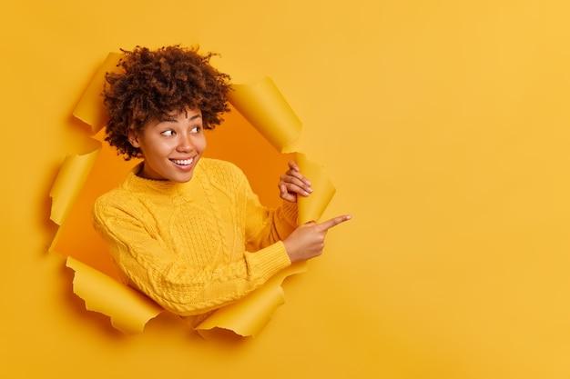 Prova questo! la giovane donna afroamericana dall'aspetto piacevole allegra indica lo spazio vuoto della copia