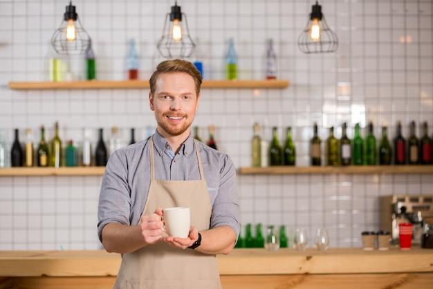 この飲み物を試してみてください。お茶を一杯持って、それを試してみることを提案しながら笑顔で幸せな素敵なポジティブな男