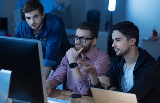 Попробуйте это проверить. интеллигентный красивый брюнет сидит со своими коллегами перед компьютером и указывает на него, работая вместе