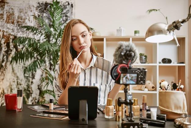 Пробует новый цвет молодая женщина-блогер пробует новый цвет помады, делая новую.