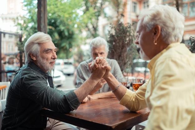 アームレスリングをしようとしています。パブの外に座って腕相撲をしようとしている2人の引退した男性